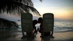 Älska par på den tropiska stranden beundrar solnedgången och kyssa långsam rörelse arkivfilmer