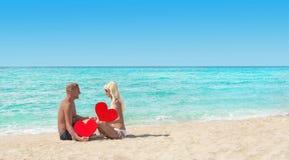 Älska par på det sandiga havet sätta på land med röda hjärtor - St-valentin Arkivfoton