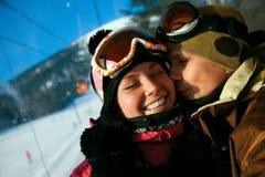 Älska par på en skidasemesterort Arkivfoto