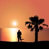 Älska par på kusten på solnedgången Royaltyfri Fotografi