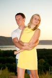 Älska par på solnedgången i sommar Arkivbild