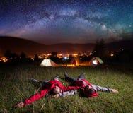 Älska par som beundrar ljusa stjärnor och ligger på gräset Royaltyfri Fotografi