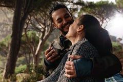 Älska par som campar i skog och att ha kaffe royaltyfri fotografi