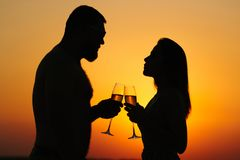 Älska par som dricker vin eller champagne under solnedgångtid, sil Arkivbilder