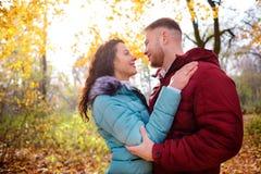 Älska par som går i höstskogen och krama arkivfoto
