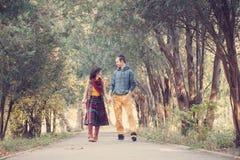 Älska par som går i parkera Arkivfoto