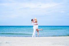 Älska par som går och omfamnar på en sommarstrand Fotografering för Bildbyråer