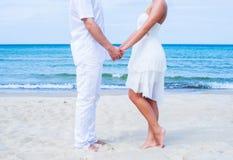 Älska par som går och omfamnar på en sommarstrand Arkivfoto
