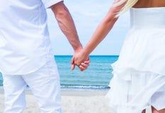 Älska par som går och omfamnar på stranden Royaltyfria Foton