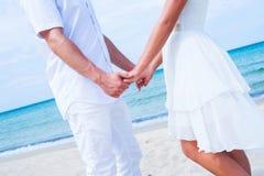 Älska par som går och omfamnar på stranden Royaltyfri Foto