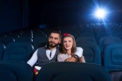 Älska par som håller ögonen på en film i den tomma bion Arkivbild
