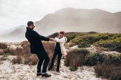Älska par som har gyckel på stranden på vinterdag Royaltyfri Bild