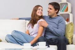 Älska par som hemma ser de på soffan Royaltyfri Foto