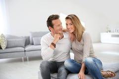 Älska par som hemma sitter att le Royaltyfria Bilder