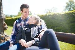 Älska par som kopplar av på en parkerabänk royaltyfri fotografi