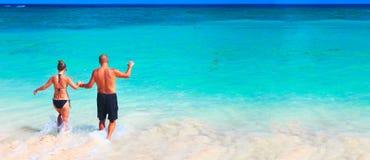 Älska par som kopplar av på stranden Arkivfoton