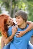 Älska par som kramar på ryggen i soligt, parkera royaltyfri foto