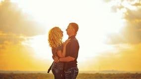 Älska par som kramar på solnedgången Royaltyfri Bild