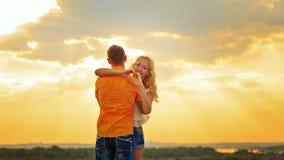 Älska par som kramar på solnedgången Royaltyfria Foton