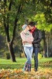 Älska par som kysser i parken i höst Arkivfoto