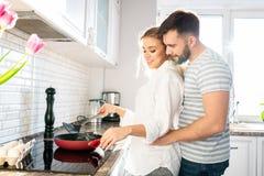 Älska par som lagar mat frukosten i kök royaltyfri fotografi