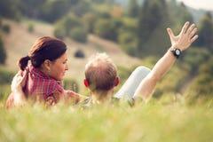 Älska par som ligger i grönt gräs på ängen royaltyfri bild