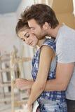 Älska par som omfamnar hemmastadd renovering Arkivfoton