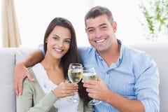 Älska par som rostar vinexponeringsglas hemma Royaltyfri Bild