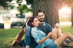 Älska par som rymmer sig sammanträde på en trädstam Arkivbild