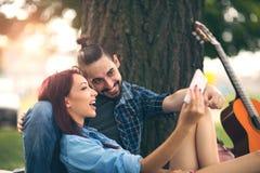 Älska par som rymmer sig sammanträde på en trädstam Royaltyfri Foto