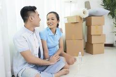Älska par som sitter på golv i nytt hus royaltyfri bild