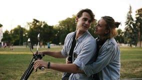 Älska par som spenderar ett avslappnande ögonblick som sitter tillsammans på en cykel i en nära omfamning Flickan kysser ömt henn arkivfilmer