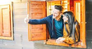 Älska par som tar en selfie utanför fönstret av deras trähus - unga vänner som tar bilder med mobiltelefonkameran arkivfoto