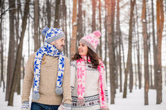 Älska par som till varandra ser och omfamnar i vinter, parkera Bärande kulöra lock och scarves Älska varma händer till varje othe Royaltyfria Foton