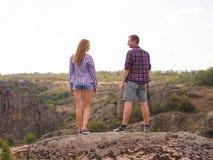 Älska par som tycker om en härlig sikt som överst står av ett berg arkivfoton