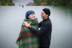 Älska par som utomhus slås in i plädsammanträde på berget på solnedgång Skjutit från ett fartyg Man och kvinna som tillsammans re Royaltyfri Foto