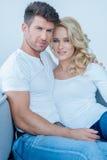 Älska sittande koppla av för par på en soffa Fotografering för Bildbyråer