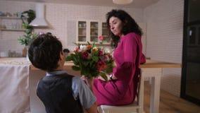 Älska sonen som gratulerar mamman med blommor stock video