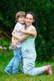 Älska sonen som kramar hans lyckliga moder parkera in royaltyfri foto