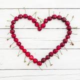 Älska symbolet av körsbäret på den vita lantliga tabellen Lekmanna- lägenhet Top beskådar Sommarbär Arkivfoton
