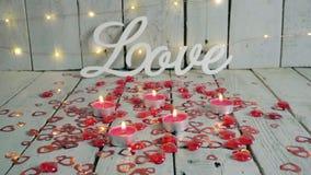 Älska tecknet med röda hjärtor omkring och stearinljus som tänds upp Ljus på backround red steg arkivfilmer