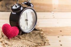 Älska tid, retro klocka med förälskelsehjärta på wood bakgrund Fotografering för Bildbyråer
