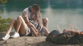 Älska tonåringparomfamningar, medan koppla av på campingplatsen på skogrivershore Lägereld på förgrund arkivfilmer