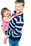 Älska ung broder som bär hans syster Arkivfoton