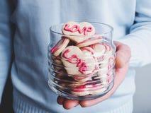 Älska ung man som rymmer ett exponeringsglas med en doftande kaka royaltyfria bilder