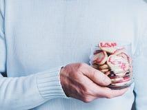 Älska ung man som rymmer ett exponeringsglas med en doftande kaka arkivbilder