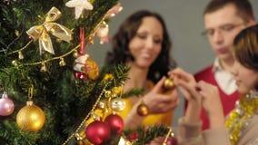Älska uppfostrar att hjälpa deras dotter att dekorera julgranen, magiska ögonblick royaltyfri bild