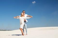 Älskar ett parinnehav händer, har uppsättningen en framsida till den varma solen bland vita sander Royaltyfri Bild