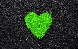 Älskar grön färg för ufon, moderiktig färg, hjärta på den svarta texturerade bakgrunden, stenar, grus och singel, tapeten, valent royaltyfria foton