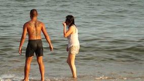 Älsklingar spenderar badning för sommarsemestertid på vattnet av den vita sandiga stranden arkivfilmer